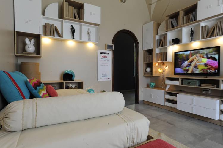 DORMITORIO PARA UNA JOVEN. Mueble tetris con luz sobre la cama y biblioteca con nichos.